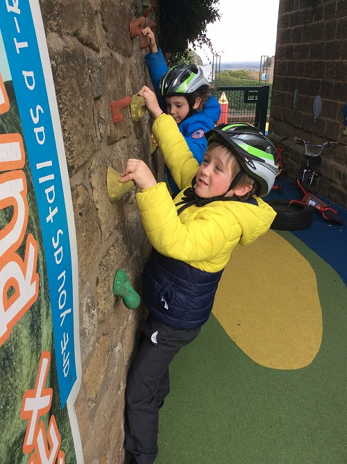 child onclimbing wall at Crich infants school