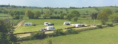 caravans in a field with St. Mary's Church, Crich in the background
