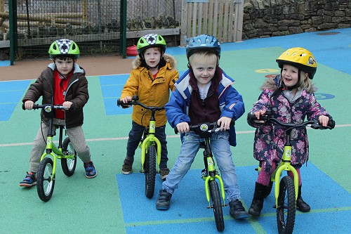picture of 4 children on balance bikes